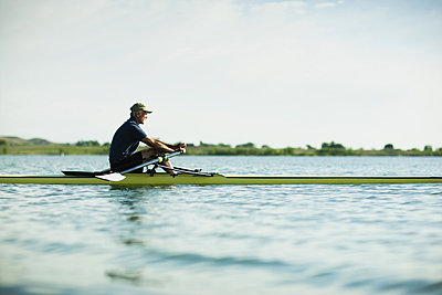 A middle-aged man in a rowing boat on the water. - p1100m876297f by Jamie Kripke