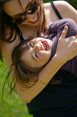 Cheerful mother and daughter embracing at park - p1166m985618f by Cavan Images