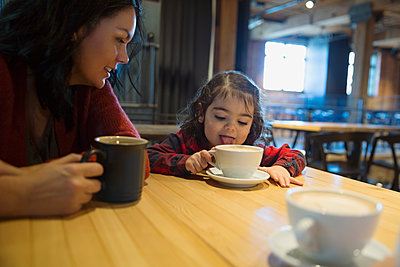 Mother watching daughter lick hot cocoa in a cafe - p1192m1128029f by Hero Images
