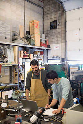 Male design professional engineers working at laptop in workshop - p1192m1202132 by Hero Images