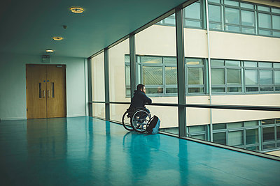 Handicapped man on wheelchair looking out from glass pane - p1315m1579181 by Wavebreak