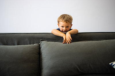 Blond boy behind sofa - p1640m2254826 by Holly & John