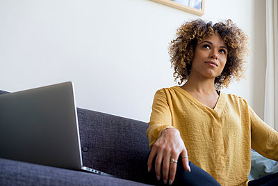 Young woman sitting on couch at home next to laptop - p300m1535263 by harry + lidy