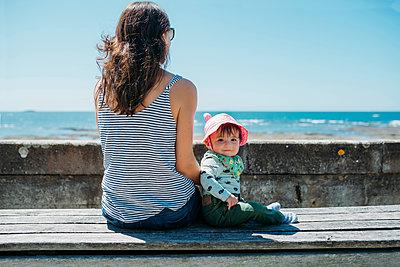 France, mother and baby girl sitting on a bench at beach promenade - p300m2004338 von Gemma Ferrando
