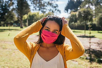 Close-up of young woman wearing mask standing in park during sunny day - p300m2206596 by Daniel Sierralta