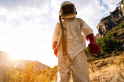 Male astronaut wearing space suit standing on mountain against sky during sunny day - p300m2221294 by Jose Luis CARRASCOSA