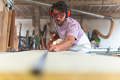 Male carpenter using tape measure while working in workshop - p300m2251992 by Josu Acosta