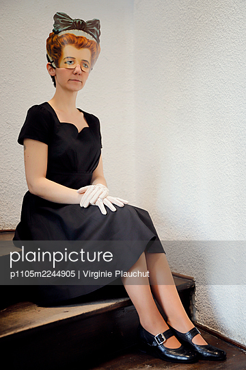 Woman in black dress and mask in the stairwell - p1105m2244905 by Virginie Plauchut