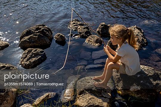 Mädchen angelt am Seeufer - p1355m1574069 von Tomasrodriguez