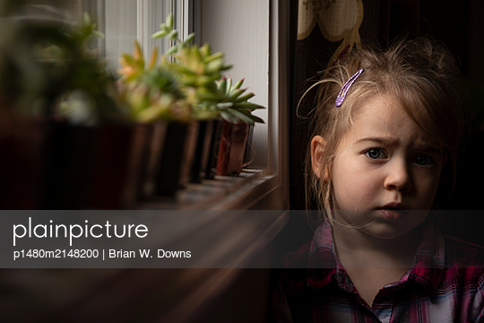 Portrait of a young girl by succulents in a window - p1480m2148200 by Brian W. Downs