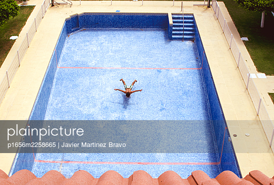 man in a pool without water pretending to dive - p1656m2258665 by Javier Martinez Bravo