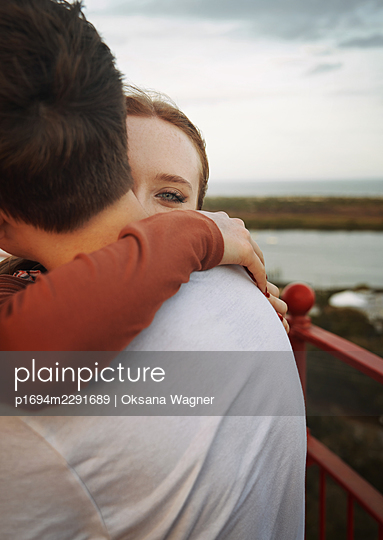 Happy young woman cuddling with her boyfriend at the panoramic viewpoint   - p1694m2291689 by Oksana Wagner