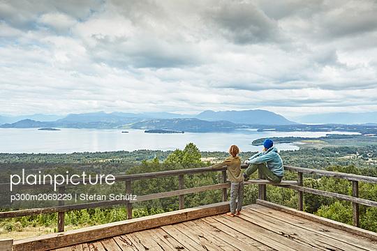 Chile, Puren, Nahuelbuta National Park, woman with son on observation terrace overlooking the lake - p300m2069229 by Stefan Schütz
