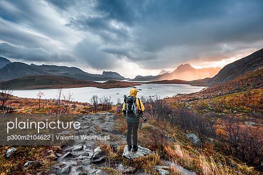 Norway, Lofoten Islands, Hiker on the way to Kvalvika Beach - p300m2104622 by Valentin Weinhäupl