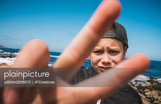 Boy standing by the ocean near Carmel, California, USA, making Victory Sign, looking at camera. - p924m2208572 by JFCreatives
