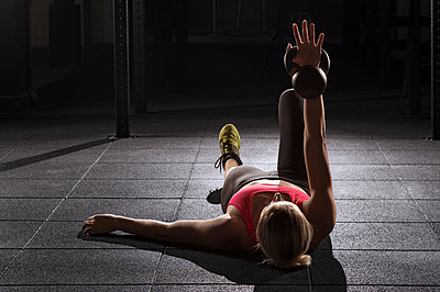 Female athlete lifting kettle bell while lying on floor at gym - p1166m1154116 by Cavan Images