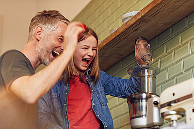 Playful father and daughter in kitchen preparing a smoothie - p300m2189328 by Maya Claussen