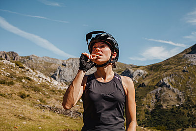 Woman wearing cycling helmet eating biscuit while standing against mountain at Somiedo Natural park, Spain - p300m2225188 by David Molina Grande