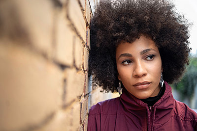 Afro young woman day dreaming while leaning on brick wall - p300m2242630 by Ignacio Ferrándiz Roig