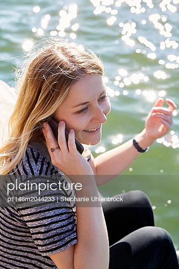 Frau telefoniert am See - p1146m2044233 von Stephanie Uhlenbrock