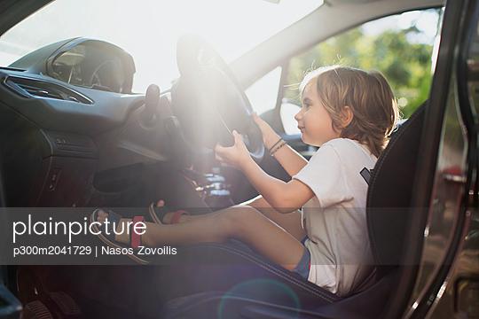 Happy little boy sitting on driver's seat in a car - p300m2041729 von Nasos Zovoilis