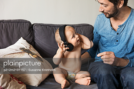 Father with baby on sofa - p312m2191157 by Susanne Kronholm
