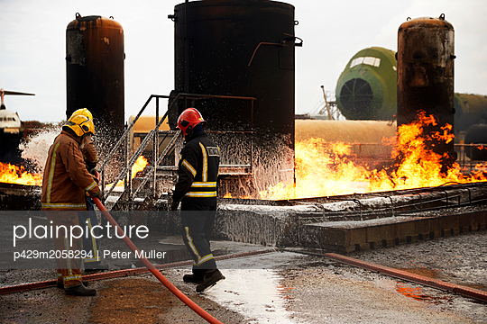 Firemen training, spraying firefighting foam onto oil storage tank fire at training facility - p429m2058294 by Peter Muller