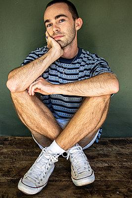 Mann in Shorts und Turnschuhen sitzt auf einem Holztisch, Portrait - p1640m2244962 von Holly & John