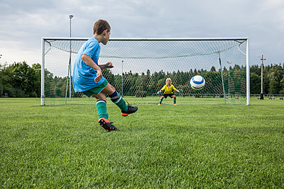 Young football player kicking ball in front of goal with goalkeeper - p300m1580799 von Fotoagentur WESTEND61