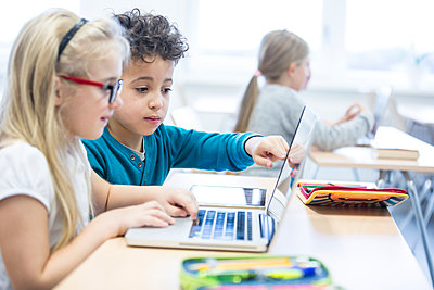 Schoolboy and schoolgirl using laptop together in class - p300m2005285 by Fotoagentur WESTEND61