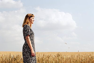 Young woman wearing dress with floral design standing in grain field - p300m2131858 by FL photography