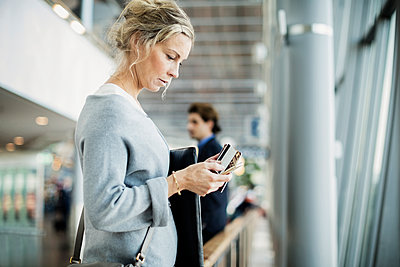 Side view of businesswoman using smart phone at airport - p426m1114706f by Maskot