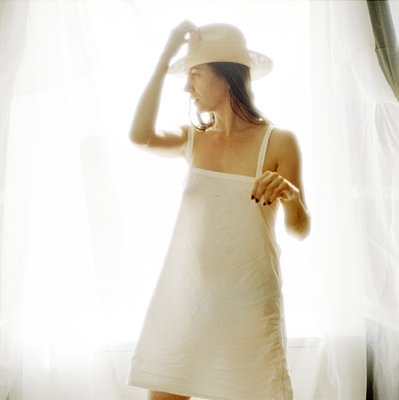 Woman standing in front of window, putting on hat - p675m922861 by Marion Barat