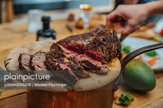 Chef arranging slice of cooked tomahawk steak in wooden plate at kitchen - p300m2256238 by Mareen Fischinger