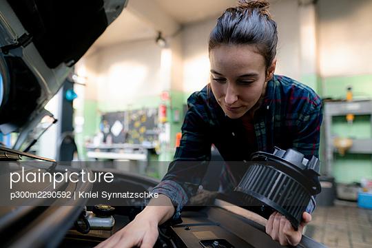 Female mechanic examining car engine at repair shop - p300m2290592 by Kniel Synnatzschke