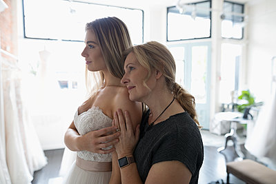 Affectionate bride and mother at wedding dress fitting - p1192m1583305 by Hero Images