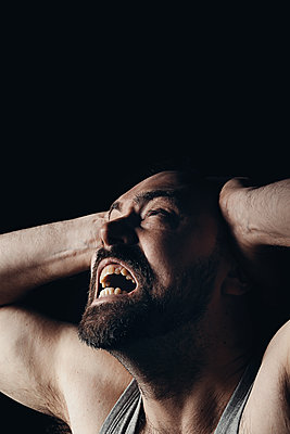 Bearded man with a suffering expression on a black background  - p1540m2100963 by Marie Tercafs