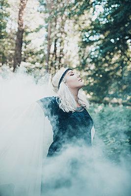 Blonde Frau in einem Märchenkostüm im Wald - p1628m2211443 von Lorraine Fitch