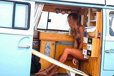Laughing young woman with surfboard in van - p300m1505196 by Simona Pilolla