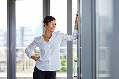Businesswoman standing in office looking out of window - p300m2012964 von Rainer Berg