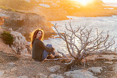 Redheaded young woman sitting at the coast at sunset, Ibiza, Spain - p300m2159922 by VITTA GALLERY