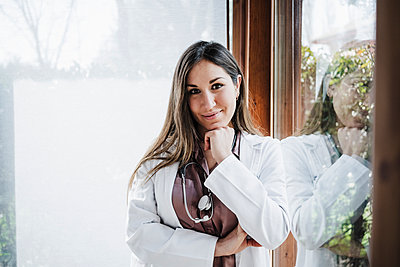 Smiling female doctor with hand on chin leaning on window - p300m2265719 by Eva Blanco