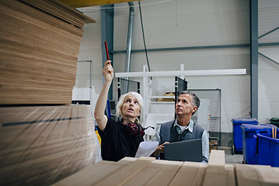 Mature woman discussing with colleague while examining wooden planks at industry - p426m1537066 by Maskot