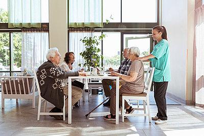 Nurse massaging shoulders of senior woman having breakfast with friends at nursing home - p426m2072545 by Kentaroo Tryman