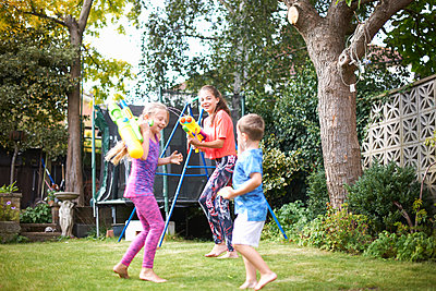 Boy and his sisters having water gun fight in garden - p429m1494614 by Peter Muller