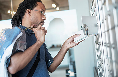Black man gathering mail from post office box - p555m1312049 by JGI/Tom Grill