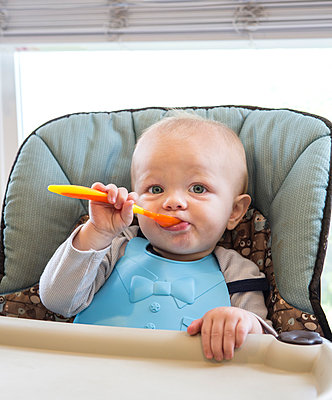 Caucasian baby boy eating in high chair - p555m1411722 by Sam Diephuis