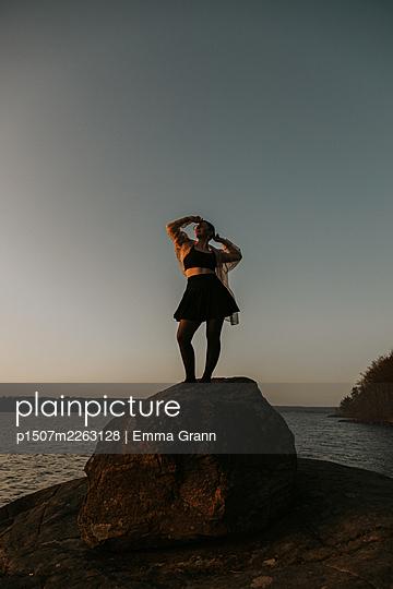 Girl in miniskirt on a rock - p1507m2263128 by Emma Grann
