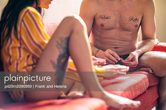 Hipster couple playing cards on sofa - p429m2090959 by Frank and Helena