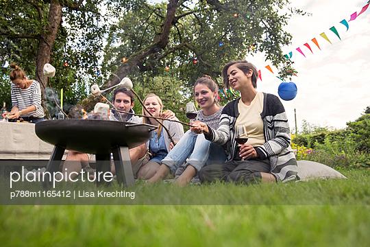 Freunde rösten Marshmallows  - p788m1165412 von Lisa Krechting